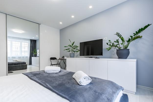 Slaapkamer in een klein appartement met een groot bed en witte muren
