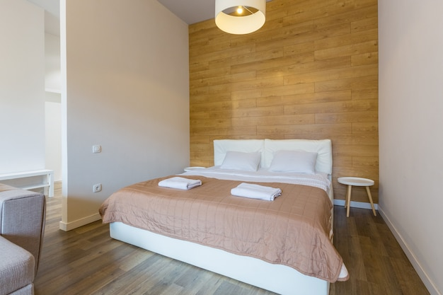Slaapkamer in een klein studio-appartement met een groot bed en witte muren