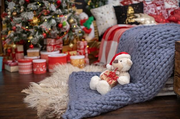Slaapkamer interieur in donkere decoratie ingericht voor kerstmis. het bed met donkerblauw linnen en veel kussens is bedekt met een wollen deken van hypergroot schaapgaren