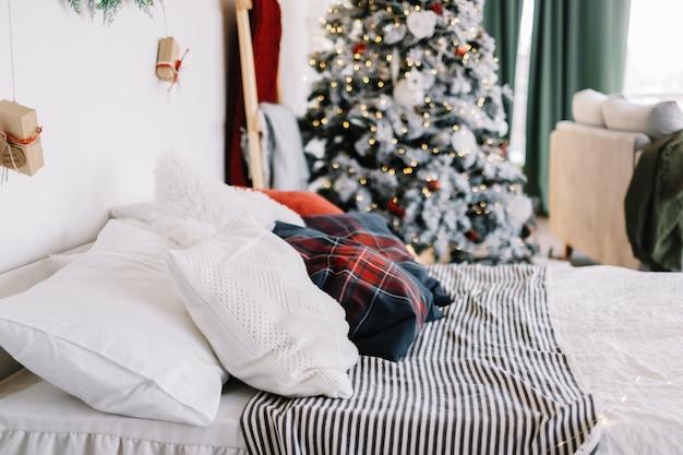 Slaapkamer interieur met groot bed en kerstboom met decoraties.
