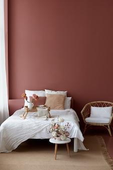 Slaapkamer interieur van rieten fauteuil, bed en kleine rieten tafel erop voor het ontbijt met een roze muur