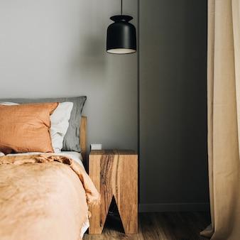Slaapkamer met bed, gember sprei, kussens, eikenhouten nachtkastje, design hanglamp, houten vloer.
