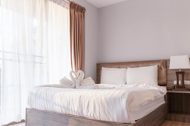 Slaapkamer met handdoek gevouwen in zwaanvorm op laken