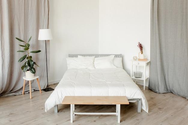 Slaapkamer met houten meubels in scandinavische stijl en ficusplant op nachtkastje