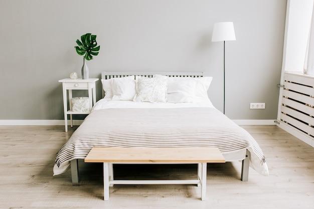 Slaapkamer met houten meubels in scandinavische stijl en monstera-plant op een nachtkastje van een boomstam