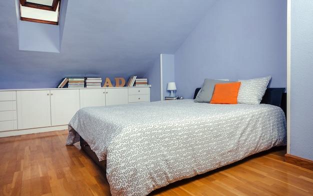 Slaapkamer op zolder met tweepersoonsbed en ladekast met boeken