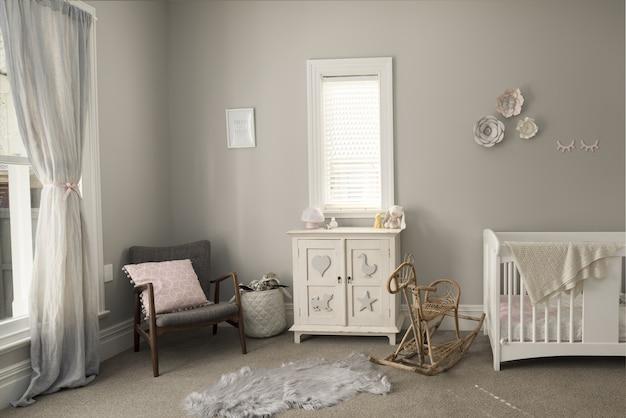 Slaapkamer van een baby met lichtgekleurde meubels en muren