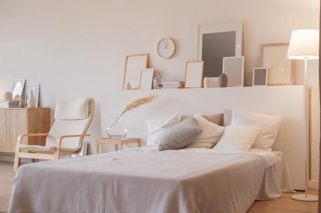 Slaapkamerinterieur met staande lamp en plantachtige fotolijsten.