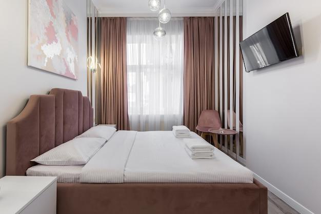 Slaapkamerinterieur, moderne stijl, groot bed, lichte kleuren, wit, roze, beige