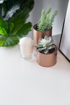 Slaapkamerwerkhoek gedecoreerd met koperen vaas met kunstmatige plant erin en witte kaars in glas op crèmekleurig gespoten werktafel met grijs geschilderde muur