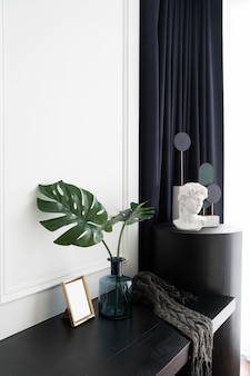 Slaapkamerwerkhoek gedecoreerd met kunstplant in glazen vaas en gedecoreerde minimale sculptuur in moderne klassieke stijl