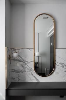 Slaapkamerwerkhoek met compositie van gouden roestvrijstalen spiegel met witte marmeren muur en gouden wandlamp