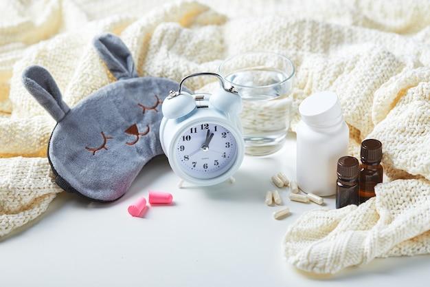 Slaapmasker, wekker, oordopjes, etherische oliën en pillen. gezond nachtrust creatief concept. goede nacht, slaaphygiëne, slapeloosheid