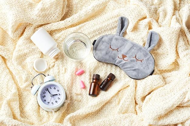 Slaapmasker, wekker, oordopjes, etherische oliën en pillen. gezond nachtrust creatief concept. plat lag, bovenaanzicht. goede nacht, slaaphygiëne, slapeloosheid