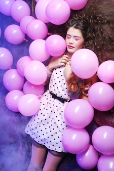 Slaapvrouw die op vloer onder ballons liggen