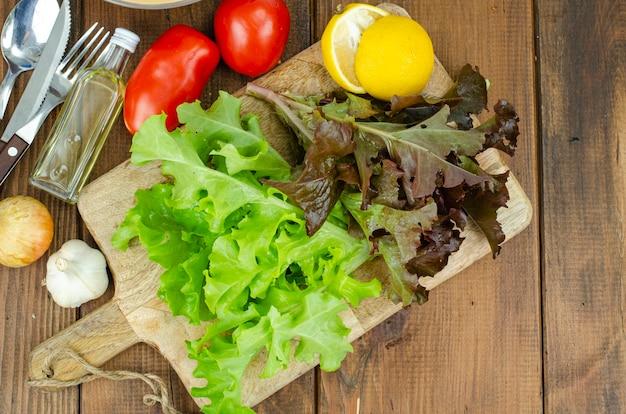 Slabladeren op houten snijplank, set kruiden om te koken. studiofoto.