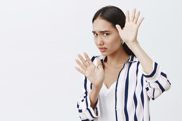 Slachtoffer van huiselijk geweld. portret van bang timide vrouw in gestreepte blouse, gezicht bedekt met opgeheven handpalmen, verdedigend tegen stoot