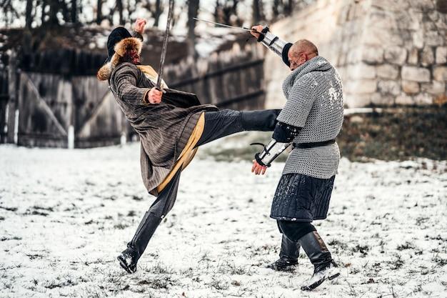 Slag van twee krijgers in harnas met wapens vechten met zwaarden in de sneeuw