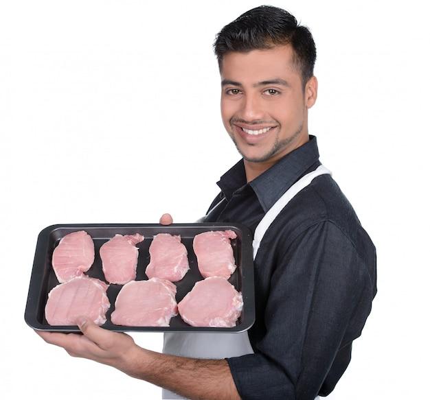 Slager die rood vlees houdt en voedsel op plaat toont.