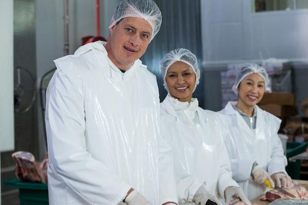 Slagers die vlees snijden bij vleesfabriek