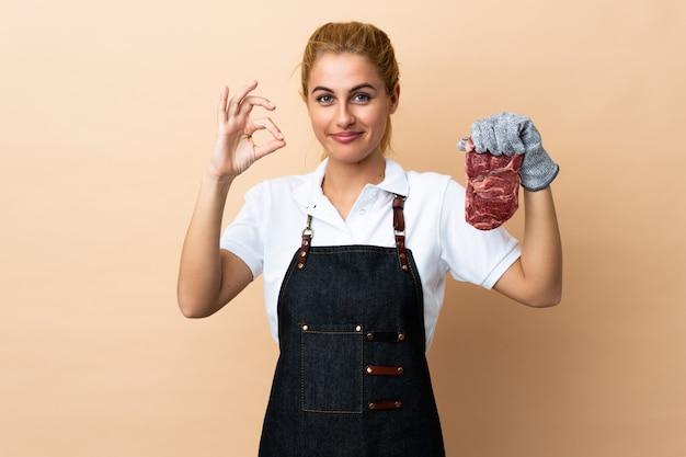 Slagersvrouw die een schort dragen en vers gesneden vlees op geïsoleerd dienen die een ok teken met vingers tonen