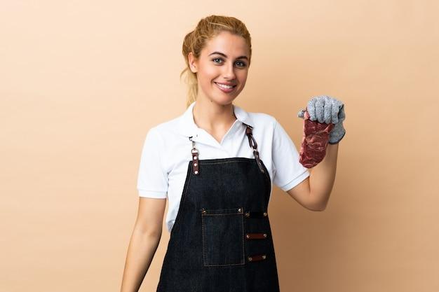 Slagersvrouw die een schort dragen en vers gesneden vlees over het toejuichen van de muur dienen