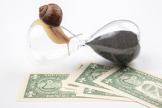 Slak kruipt op een zandloper met geld rond op wit.