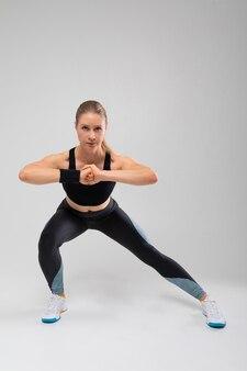 Slank blond meisje in sportlegging die zich bezighouden met fitness