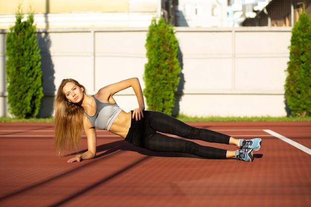 Slank fitnessmodel doet zijplankoefening buiten op de tennisbaan