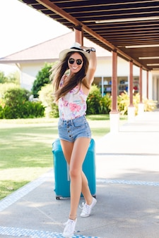 Slank gelooid jong meisje dat in een park met blauwe koffer achter haar loopt. ze draagt een spijkerbroek, een wit t-shirt, een strooien hoed, een donkere zonnebril en witte gympen. ze lacht en haar haren vliegen