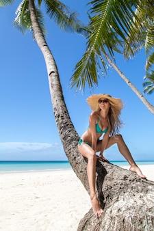 Slank gelooid meisje in blauwe bikini, grote strohoed en zonnebril die op palm zitten.