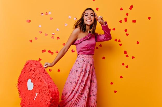 Slank gelooid meisje in trendy blouse dansen. geïnteresseerde jonge dame in roze kleren die zich voordeed op gele muur.