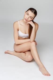 Slank gelooid vrouwenlichaam over grijs