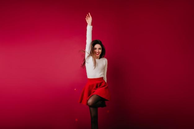 Slank gelukkig meisje in witte trui springen op bordeaux ruimte