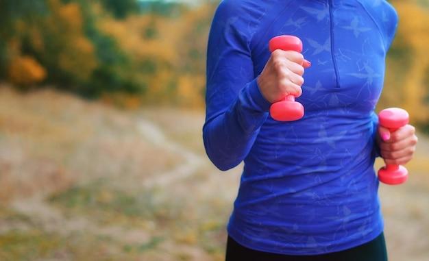 Slank jogger meisje in blauw shirt met roze halters in haar handen voert de oefening uit