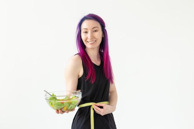 Slank jong aziatisch meisje met gekleurd haar wordt gemeten terwijl ze een meetlint hangt en een lichte groentesalade in haar handen houdt die poseren op een witte muur. gezond eten concept. copyspace.