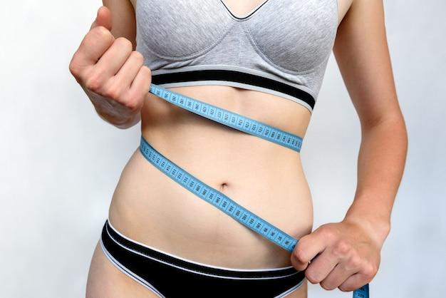 Slank jong meisje dat haar taille met blauw meetlint op grijze achtergrond meet. slank en fitnessconcept.