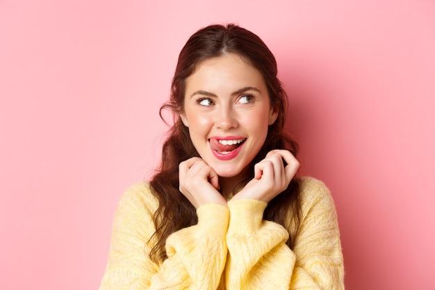 Slank jong meisje likken haar lippen en tanden, opzij kijkend met bedachtzaam gezicht, interessant idee hebben, denken, staande tegen roze muur.