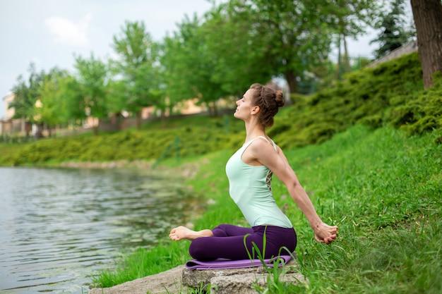 Slank kaukasisch donkerbruin meisje dat yoga in de zomer op een groen gazon door de rivier doet