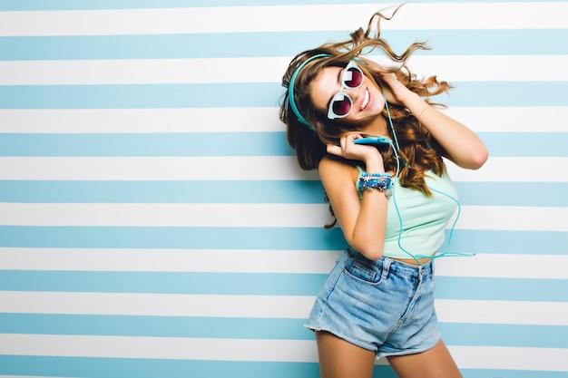 Slank lachend meisje in trendy denim shorts grappige dansende grote koptelefoon houden. aantrekkelijke gelooide jonge vrouw in zonnebril met krullend haar zwaaien koelen op gestreepte muur en glimlachen.