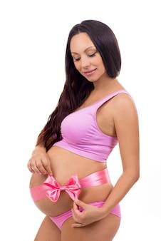 Slank lachend zwanger meisje in een roze lingerie bindt een roze strik op zwangere buik