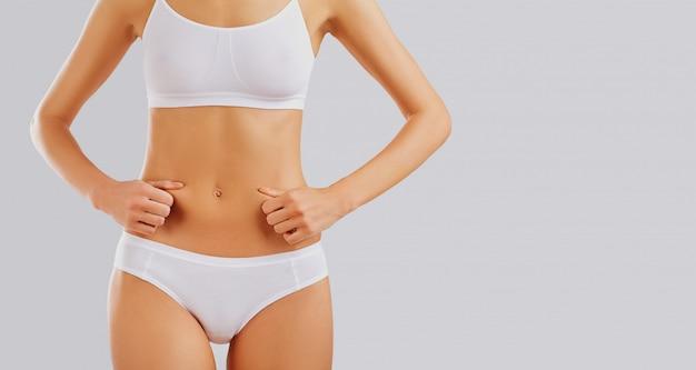 Slank lichaam van een jonge vrouw in lingerie op een grijze achtergrond.