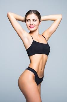 Slank lichaam van jonge vrouw in zwarte bikini. meisje met gezond sportief cijfer aangaande witte muur