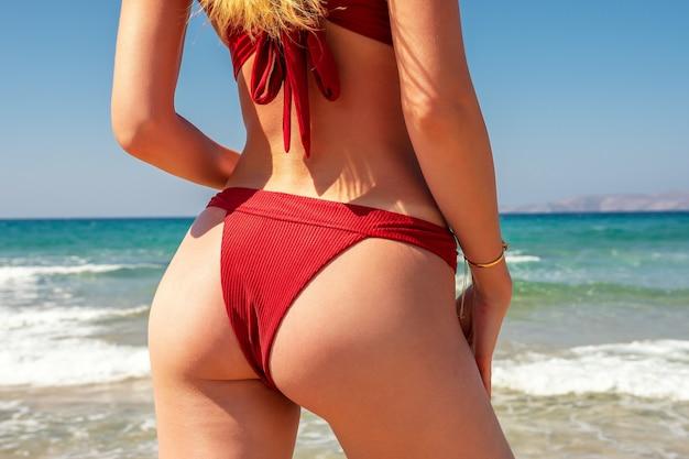 Slank luxemeisje in een rode bikini op het strand.