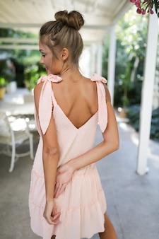 Slank meisje draagt lichtroze jurk, bedenken, stijl, haarknotje, zacht, mode, kleding, feest, evenement, buiten-, mooie armen, rug