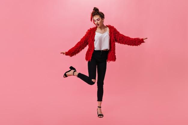 Slank meisje in donkere jeans en rode jas dansen op roze
