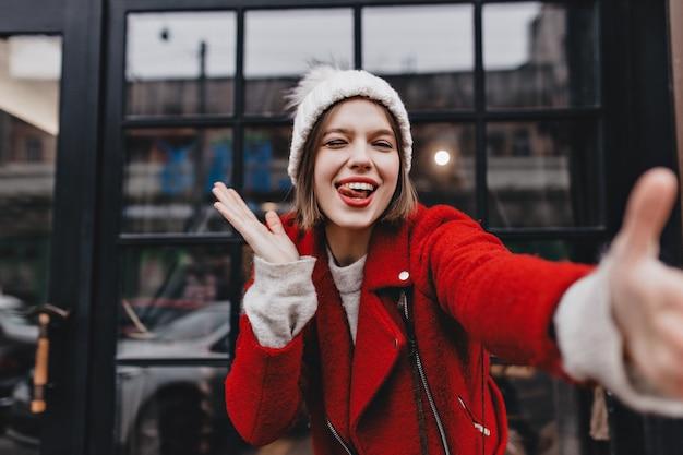 Slank meisje in een rode jas toont haar tong, knipoogt en neemt selfie op achtergrond van venster met zwart frame.