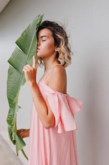 Slank meisje in lange roze jurk poseren met gesloten ogen en blad te houden. binnenfoto van doordachte jonge vrouw met golvende kapsel snuivende bloem.