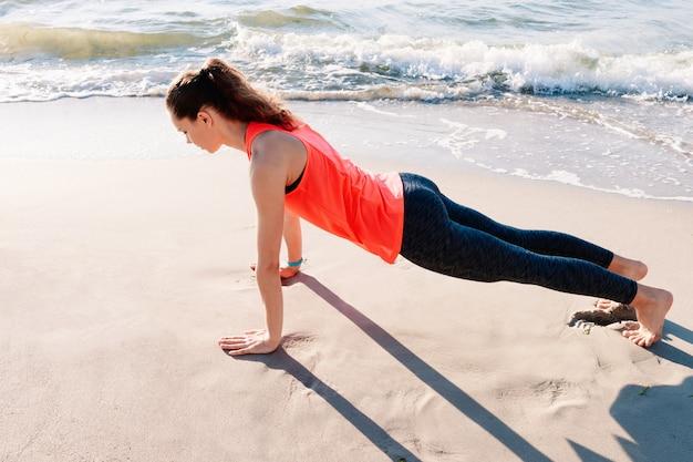Slank meisje in sportkleding die oefening in de ochtend op het strand doet