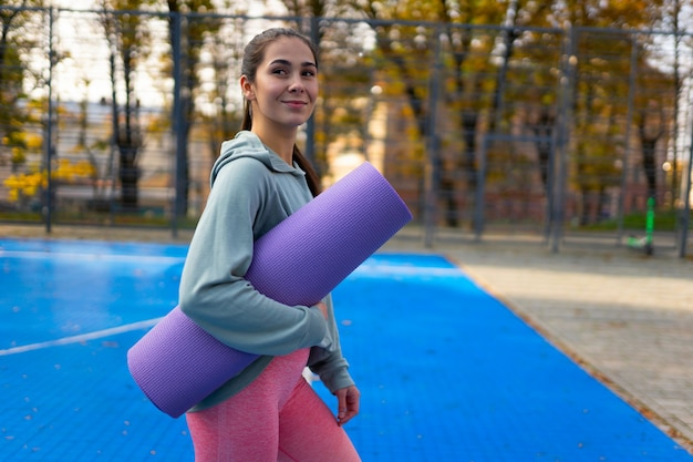 Slank meisje met een yogamat in handen